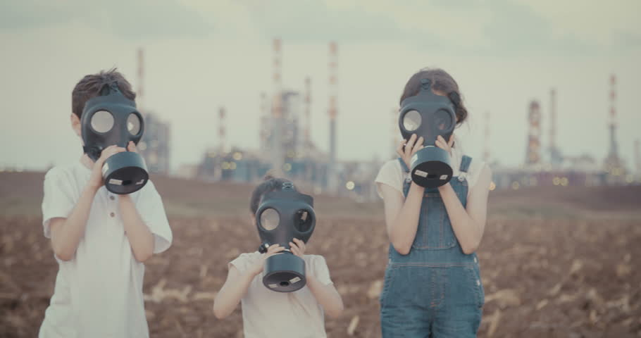 Save the planet. Kids wearing gas masks near a large oil refinery - 4K stock video clip