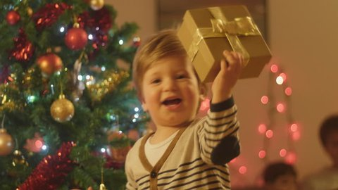 Adorable little baby boy having fun on a christmas eve at home, smiling and running around with a christmas present.