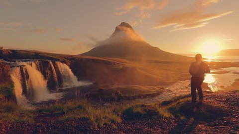 Photographer shoot a Green Mountain Peak and Kirkjufellsfoss Falls in the morning at Iceland, Summertime, slow motion