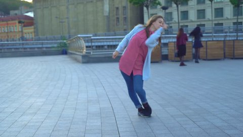 young attractive woman professional dancer does contemporary dance on a square in the street. modern extreme dances in the style of hip-hop and classical ballet.