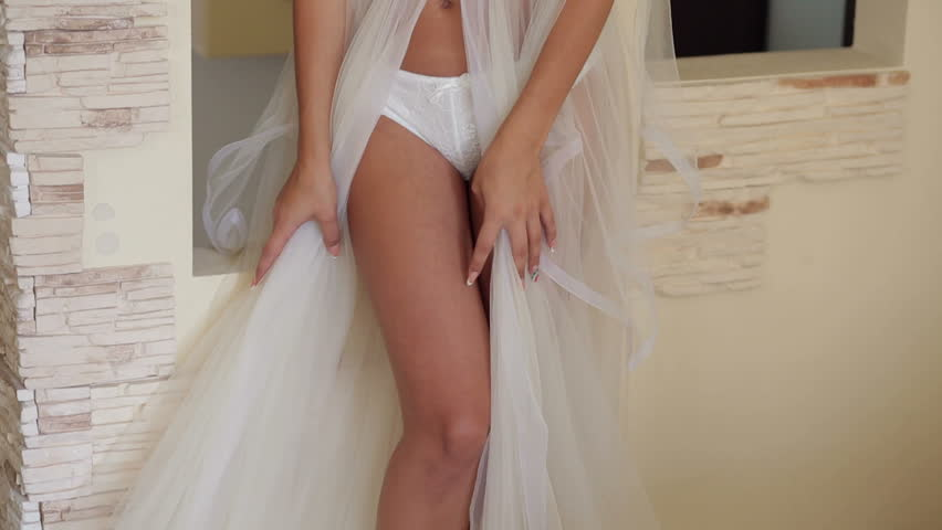 Close-up of the legs of a sexy slender girl in lingerie and translucent negligee.