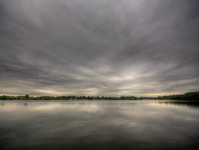 Impressive storm clouds over lake, HD time lapse clip, high dynamic range imaging.