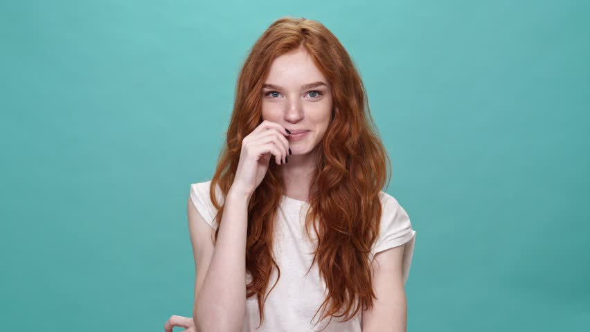 Laughing ginger woman in t-shirt looking at the camera over turquoise background | Shutterstock HD Video #31644862