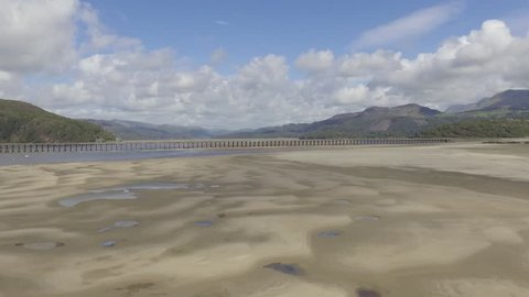 Moving aerial shot flying towards the Barmouth Viaduct (Wales) with the sand and water of the River Mawddach, looking into the Welsh hills and mountains of Snowdonia National Park.