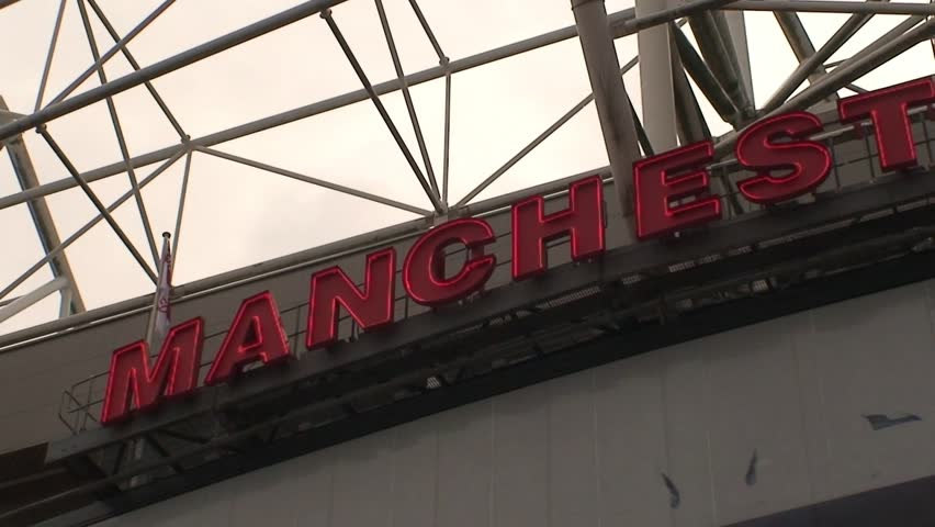Slow pan of the Neon Manchester United sign on the East Stand of Old Trafford.