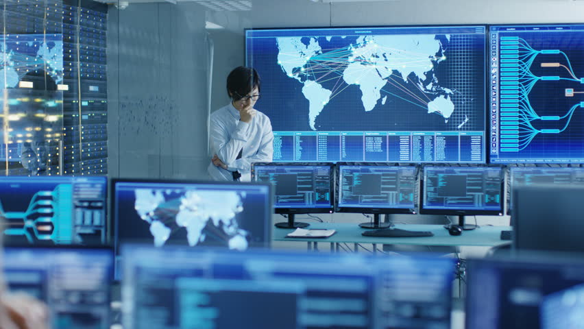 In the System Control Room Chief Engineer Thinks While Standing Before Big Screen with Interactive Map on it. Data Center is Full of Monitors Showing Graphics.  | Shutterstock HD Video #31689532