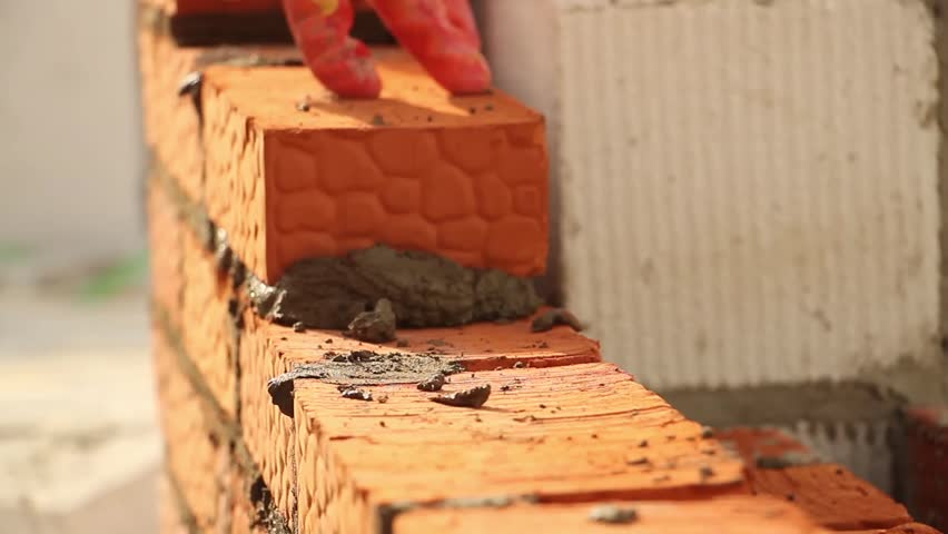 The Builder On A Building Makes Bricklaying At Construction Site Brickwork