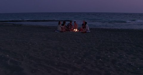 View from above of hipster friends roasting marshmallows over bonfire on the beach at night