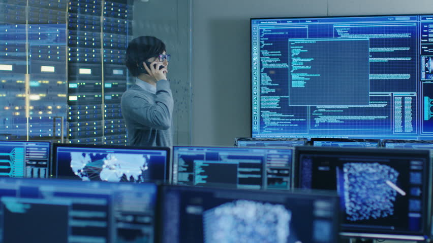 In the System Control Room IT Administrator Talks on the Phone. He's in a High-Tech Facility That Works on the Surveillance, Neural Networks, Data Mining, AI Projects. Shot on RED EPIC-W 8K  Camera. | Shutterstock HD Video #31712062