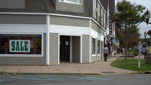 Generic corner clothing store in small town USA America day time exterior establishing shot. Unrecognizable people walk sidewalk on Main Street in distance