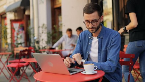 A closeup portrait of an attractive young man drinking coffe and then - working on his laptop at the cafe. Moving camera. Blurred background