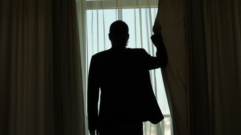 Man in casual suit stand against window, close curtains one by one, shade room from daylight. Half length medium telephoto view from behind, black silhouette of hipster guy