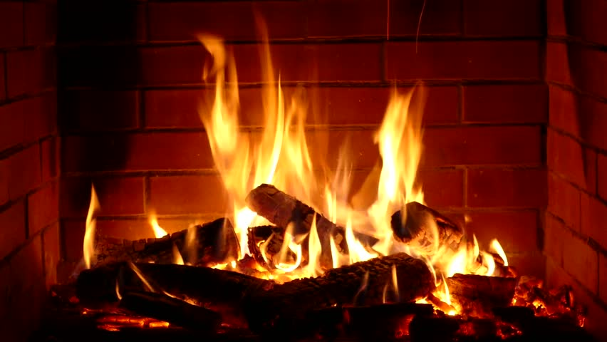 Stunning satisfying close up view on wood burning slowly with orange fire flame in cozy brickwork fireplace atmosphere