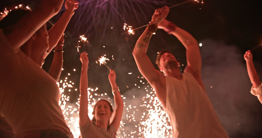 Multi-ethnic friends with arms outstretched celebrating fourth of July with sparklers, confetti and fireworks display