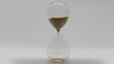 Sand running out in hourglass on white background - time lapse