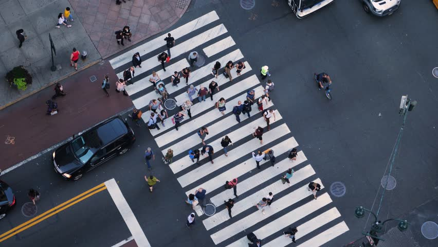 A high angle, slow motion view of pedestrians and traffic on 5th Avenue in midtown Manhattan.