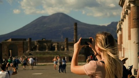 Pompeii Ruins, Italy Tourism. UNESCO World Heritage Site. Young Woman Exploring Europe.Tourist Woman Exploring Pompeii While Traveling In Italy. Woman Tourist Taking Photograph. Volcano Vesuvius