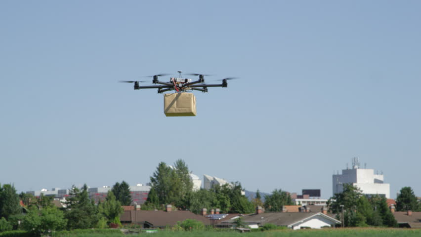 CLOSE UP: UAV drone delivery. Multicopter flying big brown package into city. Drone delivering post package to your home. Futuristic shipment by helicopter drone. Multirotor logistics and transport. | Shutterstock HD Video #31829842