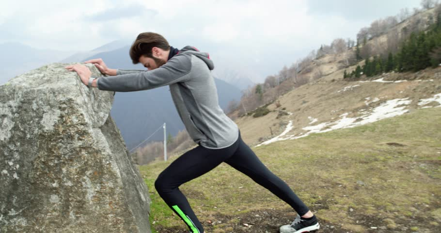 Athlete man runner warming up or cooling down stretching.Real people adult trail running sport training in autumn or winter in wild mountain outdoors nature, bad foggy weather.4k video | Shutterstock HD Video #31837930