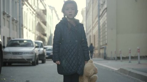 Sad little girl with teddy bear staying in the street, turning and go away.
