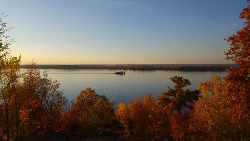 View of the river before sunset. A small ship sails along the river - push towboat. And in front of him, a motor boat floats by the shore