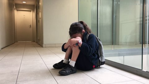 One young elementary school girl wearing school uniform and backpack sitting on a corridor floor crying. Childhood and education concept. Real people. Copy space