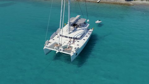 Aerial View of a Anchored Catamaran Yacht Standing with People Sunbathing on it's Deck. Boat Stands in Azure Sea Waters With Coral Reef Visible.Shot on Phantom 4K UHD Camera.
