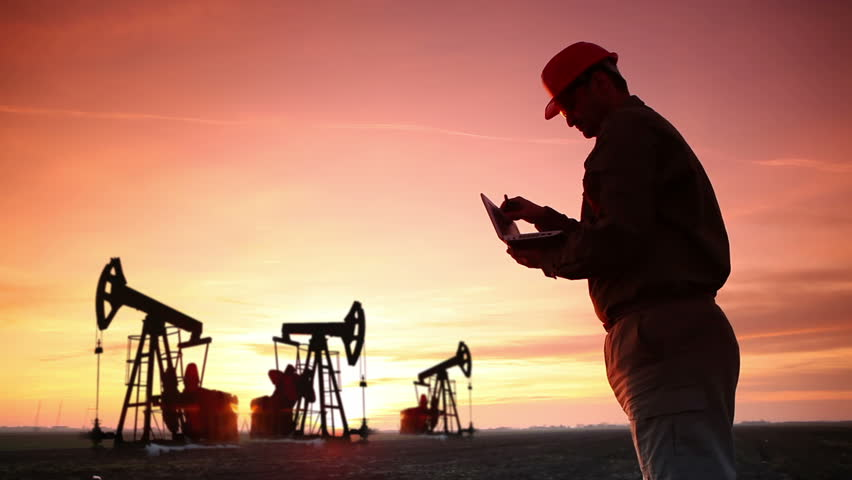 Oil Industry Pump jack with one oil worker who using a phone and typing on laptop.In a background are Silhouettes of three Pump jack at sunset light. | Shutterstock HD Video #3186604
