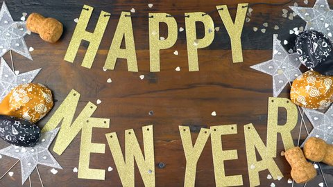 Happy New Year gold letters bunting and decorations on dark wood table overhead time lapse.