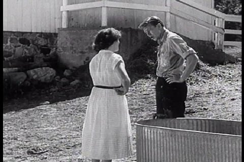 CIRCA 1950s - A quarrel between a man and woman ends with the woman being dumped in a trough full of water in this brazen 1950s clip.