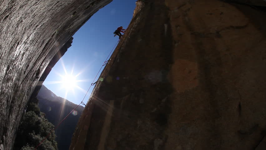 A silhouette of a female rock climber with safety harness and rope attempts to climb a boulder during the day in a national park