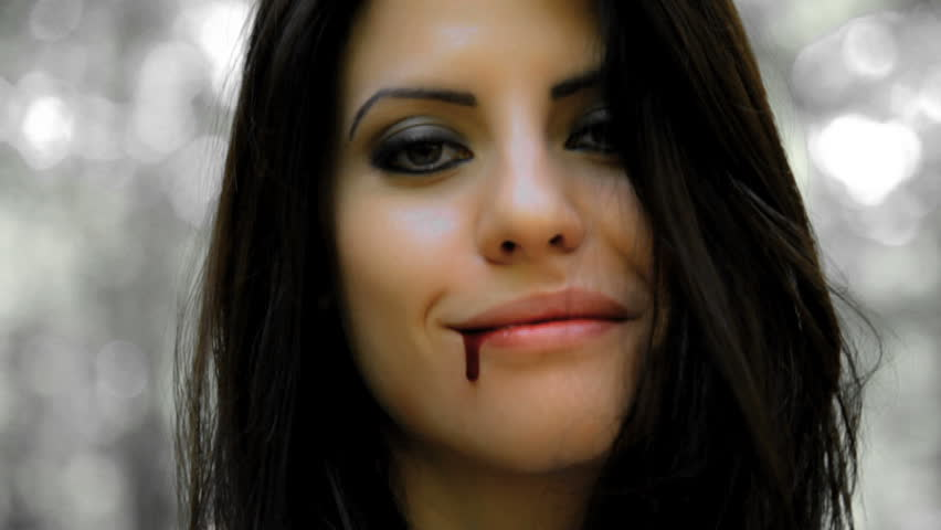 Vampire woman smiling with blood