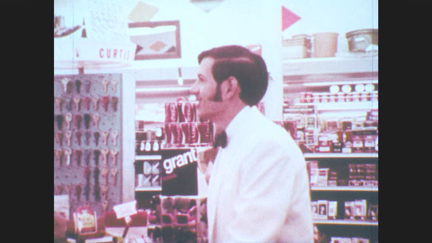 1970s: Teenager in white tuxedo jacket smiles, walks away from check out counter. People picnic next to lake.