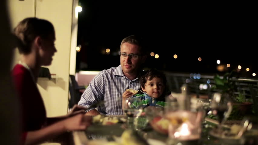Family with friends eating dinner in the evening, stabilized shot
