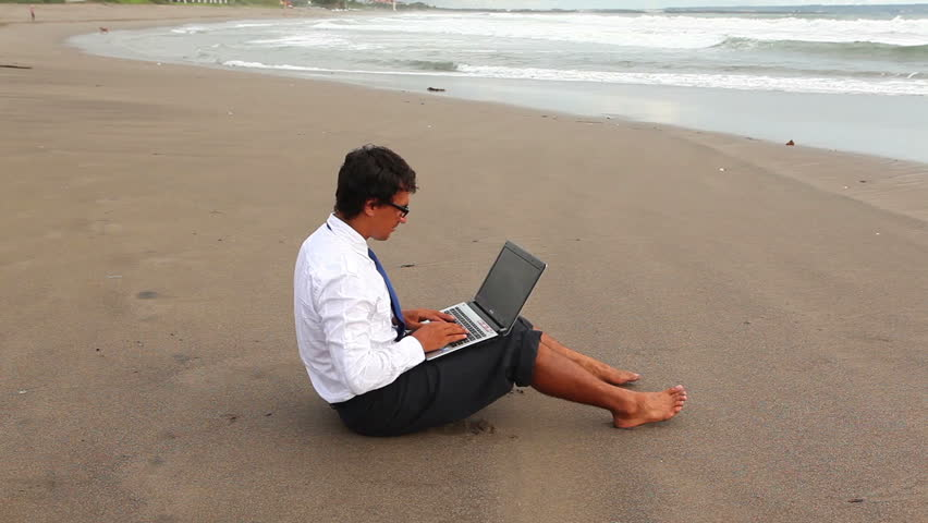 young guy in office suit printing something on laptop sitting on the beach