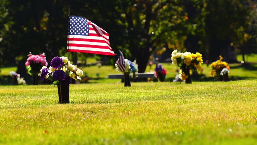 An American flag flies over the grave of a soldier in a cemetery. Flowers adorn all the graves.