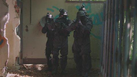 A Special Force Team walk through a open corridor.