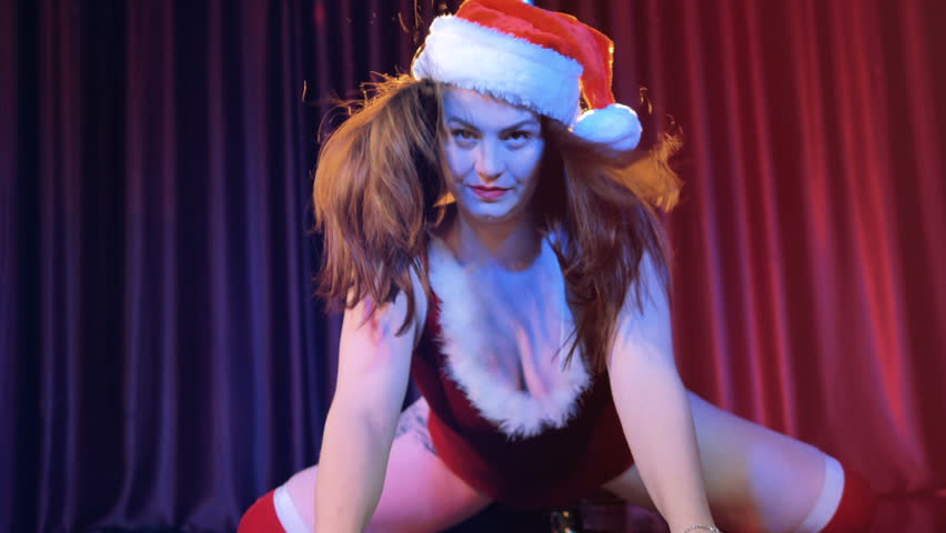 Female stripper in christmas cap sexually moving. 4K.