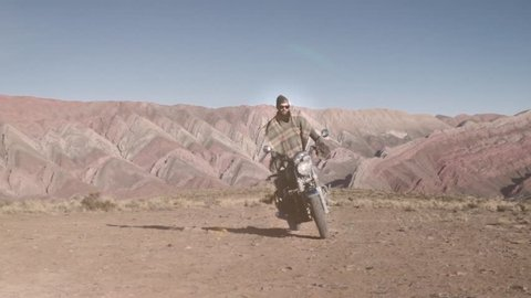 Man riding custom motorcycle in the salt flats of Salar grande in Argentina. Slow motion