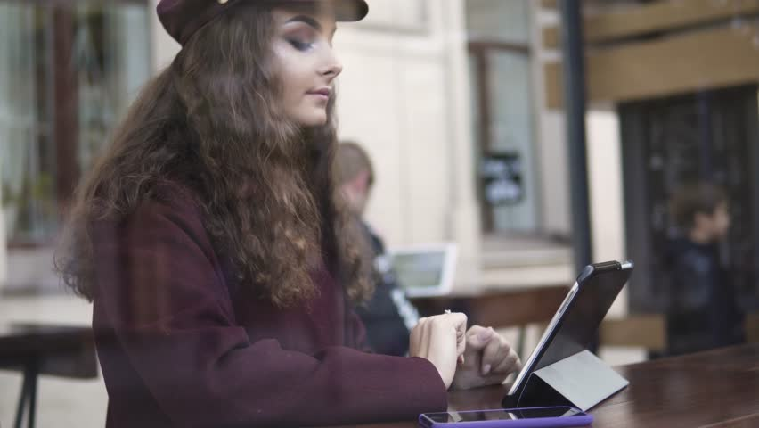 Young woman with tablet computer drinking coffee in cafe | Shutterstock HD Video #32058802