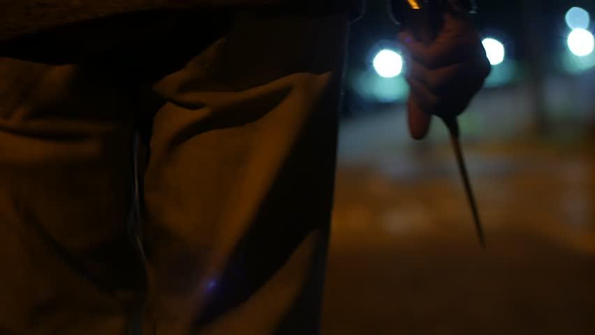 A MAN WALKS AT NIGHT HOLDING A BIG KNIFE