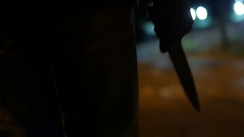 A MAN WALKS AT NIGHT HOLDING A BIG KNIFE, BLURRED BACKGROUND, WAIST AND HAND SEEN