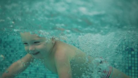 Cute blonde toddler is jumping under the water in the swimming pool and swimming there until his mother is lifting him from the water. An underwater shot