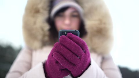 Young Caucasian woman in gloves using a smartphone in winter time.