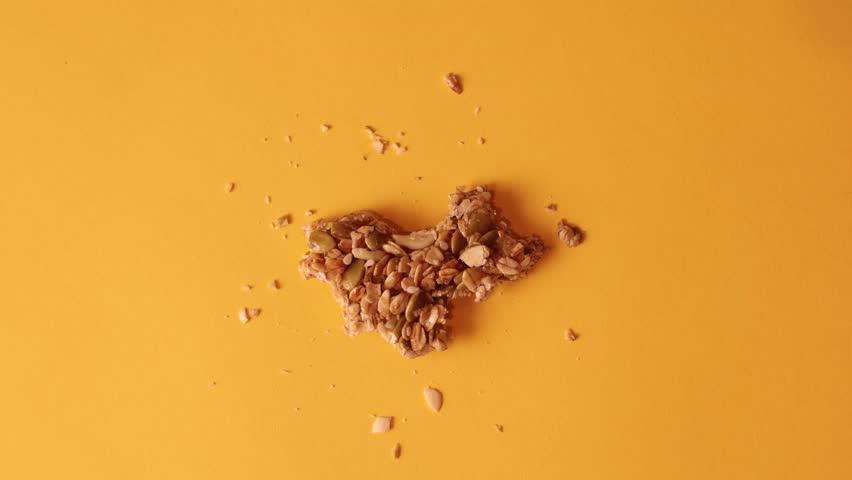 Granola bar bites stop motion on solid orange background with granola crumbs