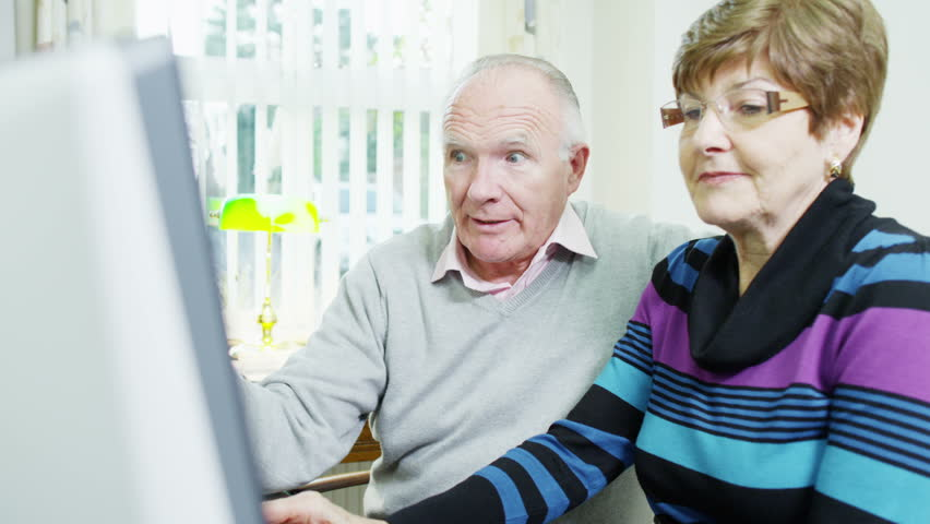An elderly couple are browsing the internet together and looking to book a holiday online