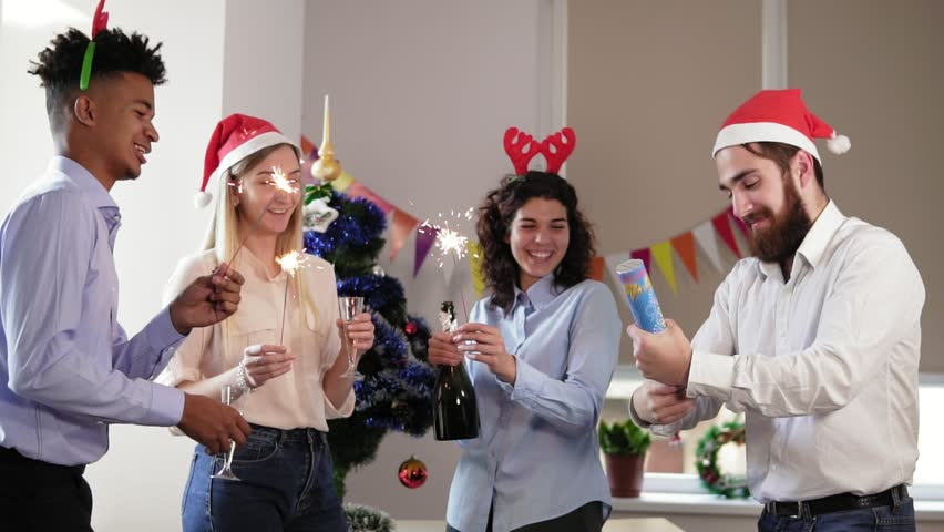 aff02e3d5f5 Happy multi-ethnic people in funny hats lighting sparklers celebrating  christmas and new year in the office