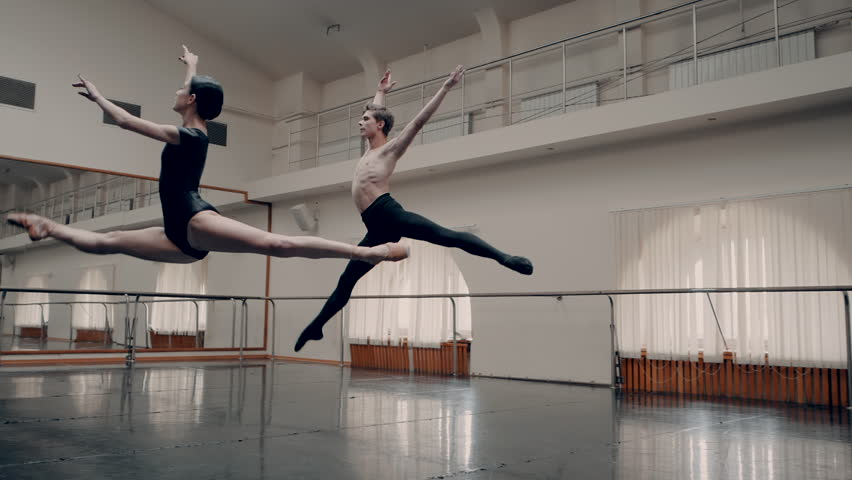 Young man practicing in classical ballet with young beautiful woman in black clothing in the gym or ballet hall. Couple jumping. Minimalism interior, sensual dance. Slow motion. adagio