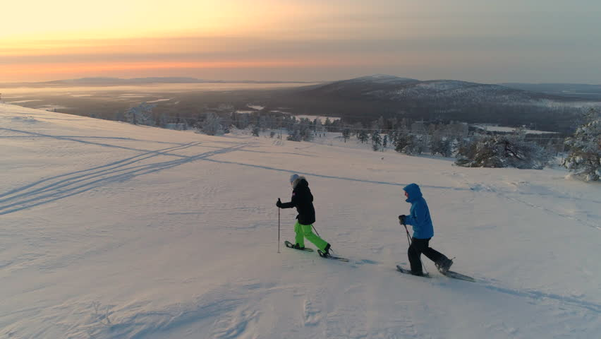 AERIAL: Active couple in warm winter ware snowshoeing on snowy mountain at sunrise. Man tour guide and woman snowshoe hiking at winter sunset. Travelers snowshoe exploring snowy Lapland mountains