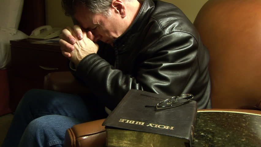A man puts down a Bible he has been reading then folds his hands in prayer.
